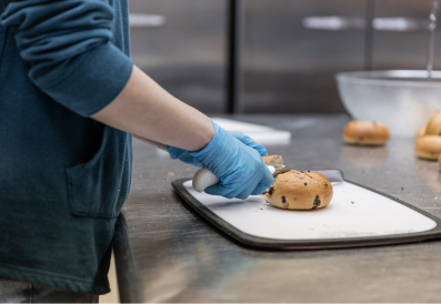 Volunteer slicing bread in a kitchen and wearing blue protective gloves